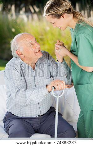 Side view of female caretaker helping senior man to get up from couch