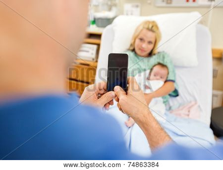 Closeup of man photographing woman and newborn babygirl through cell phone in hospital