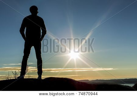As the sun sets a man gazes into the distance with his hands in his pockets whilst on top of a mountain poster