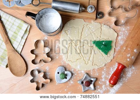 Baking holiday cookies still life shot form a high angle. Horizontal format with cookie dough, cutters, sifter, flour, rolling pin, cookie press, spoon, towel on butcher block surface.