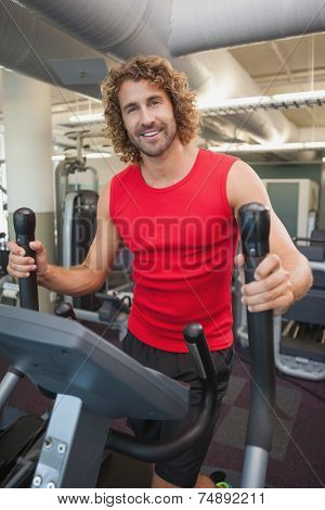 Portrait of a handsome young man working out on x-trainer in the gym