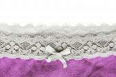 Pink cloth with lacy edge over white as a background poster