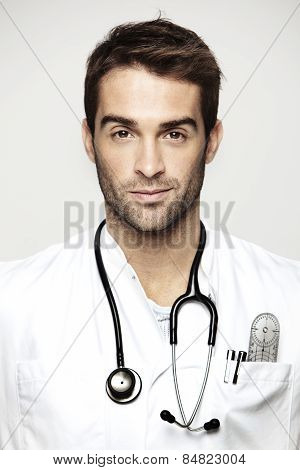 Portrait of mid adult doctor wearing stethoscope against grey background