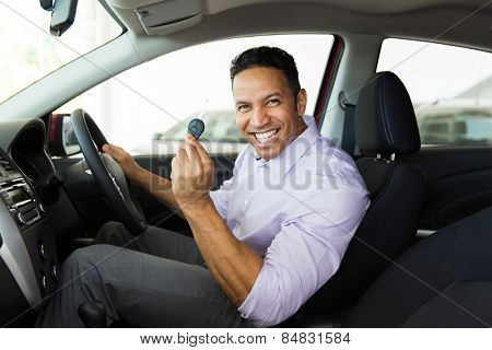handsome middle aged man showing a car key inside his new vehicle