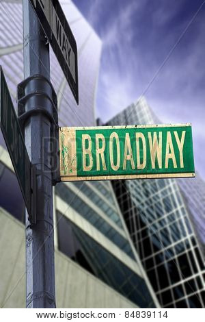 Broadway sign in front of a skyscraper with a dramatic blue sky