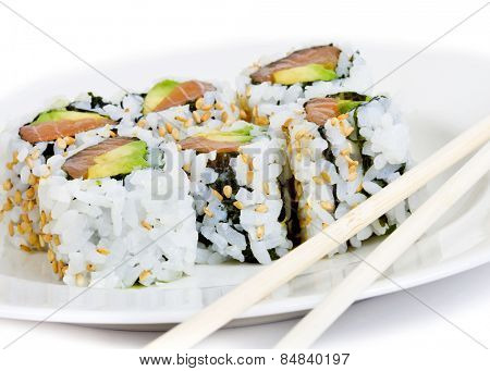 Raw fish and avocado sushi on a white plate with chopsticks