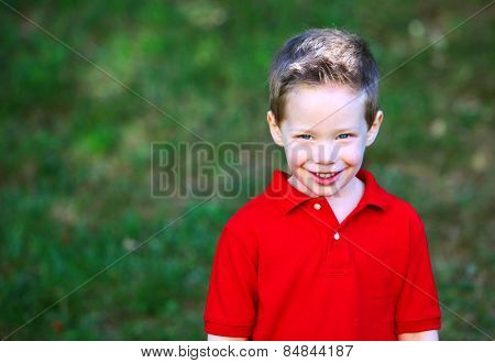 Cute boy with rosey cheeks outside portrait
