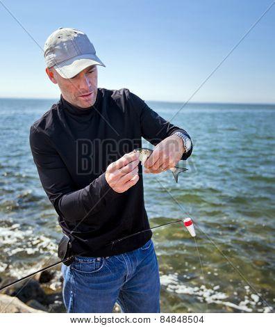 Adult male fisherman unhooking a small fish