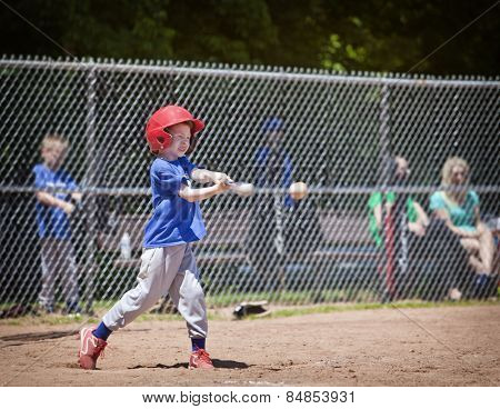 A youth baseball player takes a nice swing at the ball