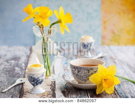 Breakfast table setting with tea, boiled eggs and spring flowers
