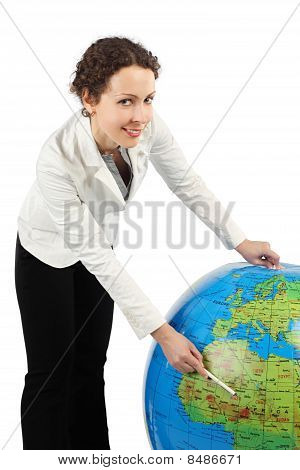 Young Woman In White Jacket Standing And Pointing At Africa On Big Inflatable Globe, Isolated