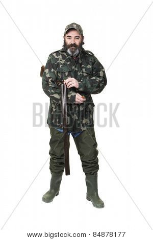 A duck hunter in waders and camo loading a double barreled shotgun on a white background.