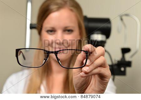 Female eye doctor holding glasses - focus on glasses