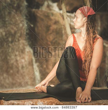 Woman practicing yoga near waterfall. Half Spinal Twist Pose. Ardha Matsyendrasana. Toned