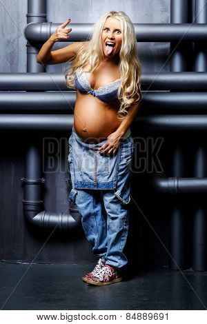 beautiful pregnant blond woman with naked belly showing her tongue and making a rock and roll gesture