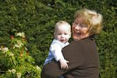 Happy grandmother holding grandson in garden poster