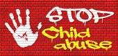 stop child abuse and neglection or violence toward children they need protaction against physical and psychological harassment graffiti on red brick wall, text and hand poster