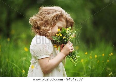 Happy little girl smelling a bouquet of flowers poster