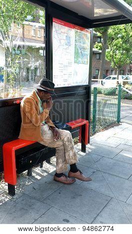 Elderly black man sitting at the bus stop