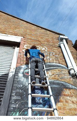 Graffiti artist paints the building wall