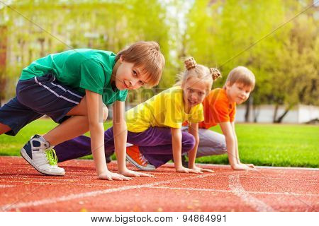 Three kids close-up in uniforms ready to run