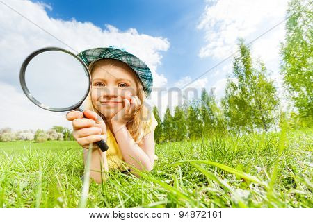 Girl holding magnifier laying alone on the green grass during beautiful summer day in park poster
