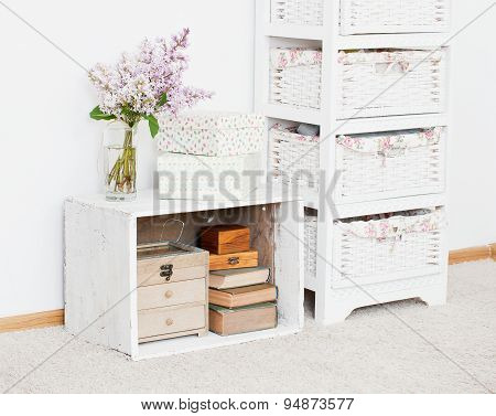 Nightstand With Flowers, Storage Boxes And Books