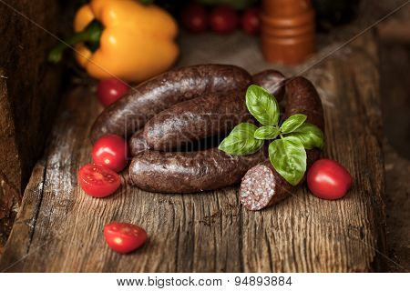 Black pudding, with cut slices, on chopping board over stone background. Krupniok really Polish bl