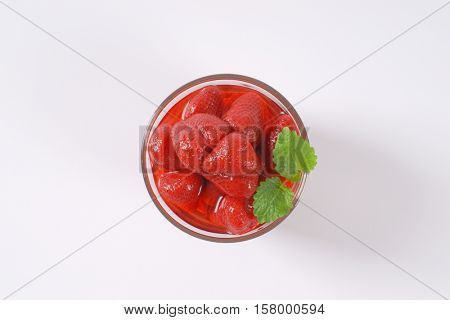glass of strawberry compote on white background