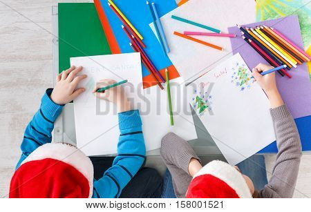 Writing letter to santa. Children in santa hats make wish list of presents for christmas. Winter holidays. Boy and girl, brother and sister draw, top view
