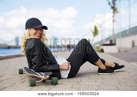 Woman with longboard sitting on the ground