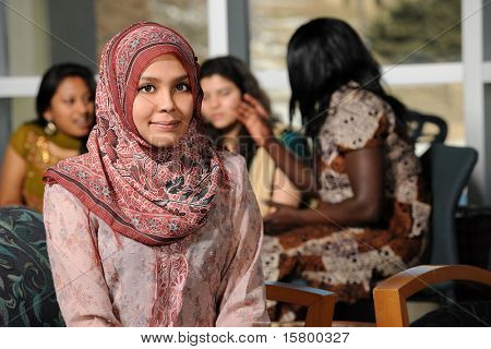 Islamic Young woman with diverse group of female students dressed in traditional clothing inside school setting