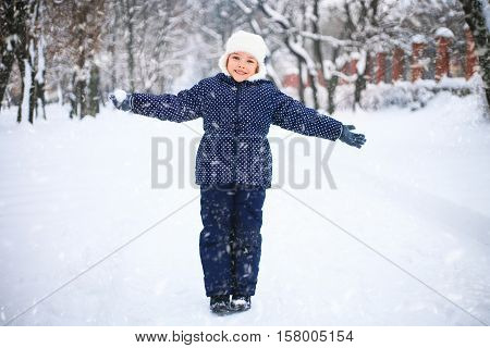 Small girl playing with snow in a park. Wonderful snowy day. The concept of childhood and the winter season.