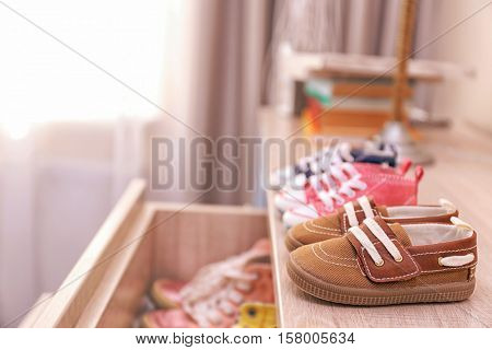 Different baby shoes on chest of drawers indoors