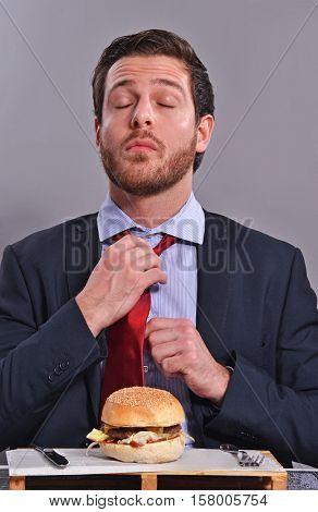 Expressive businessman adjusting tie before start eat burger.