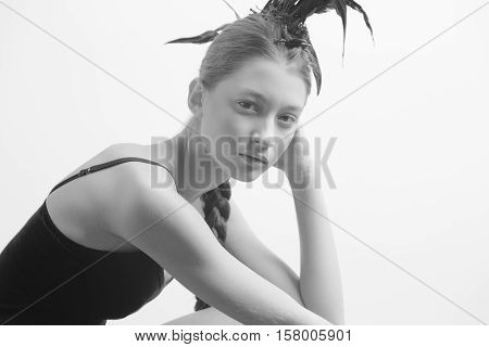Young sexy mixed race caucasian woman vogue portrait with feather mohawk accessory wearing black bodysuit sitting on wooden floor on white wall background. Fashion concept. Copy space text.