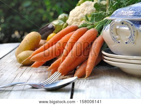 carrots and other vegetables on a table with tureen on a table
