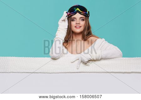 Happy woman in winter outerwear over white banner in hands at studio