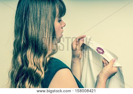 Woman holding a shirt with red kiss lipstick of her unfaithful husband - retro style