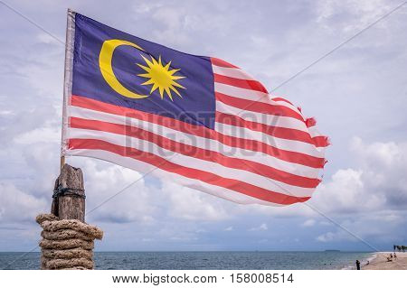 Malaysian flag attached on pole waving on beach in Langkawi island on a cloudy day