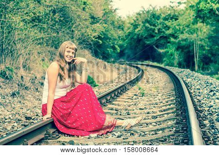 Young lady in red dress sitting on railway tracks - retro style