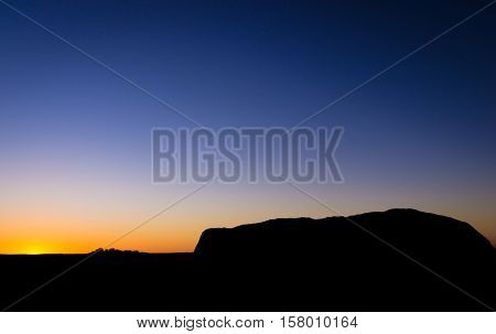 View from sunrise viewpoint of the silhouette of Uluru Ayers Rock with the sun setting behind Kata Tjuta The Olgas