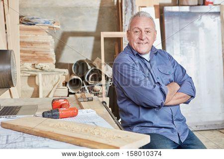 Proud senior citizen as excecutive chief at carpentry shop