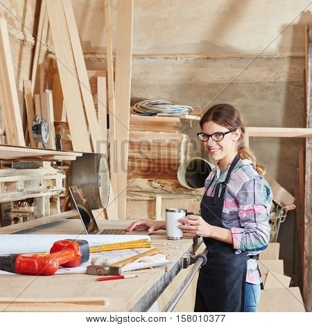 Woman as carpentry apprentice drinking coffee at workbench