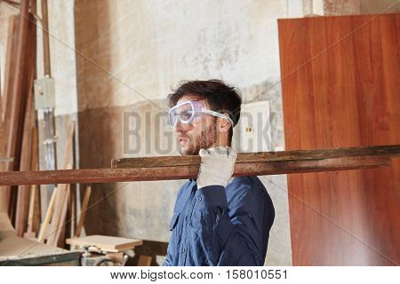 Blue collar worker carrying wood at carpentry shop
