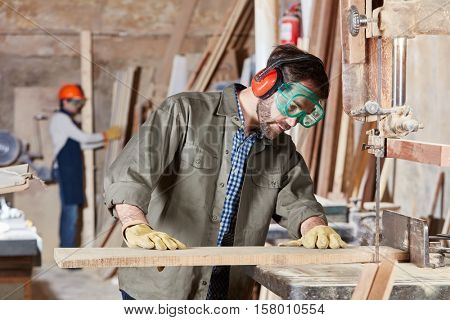 Man as carpenter processing wood with band saw
