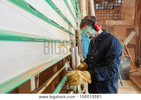 Carpenter cuts wood with vertical panel saw in carpenter�´s shop