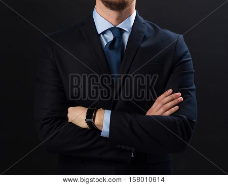 business people, style and office worker concept - businessman in suit and smartwatch over black background