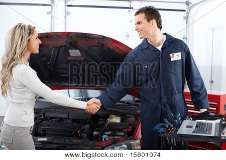 Bonito mulher mecânico e cliente na oficina de reparação automóvel.