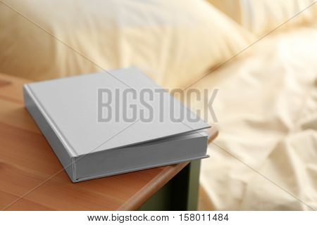 Closed book on wooden bedside table near crumpled bed